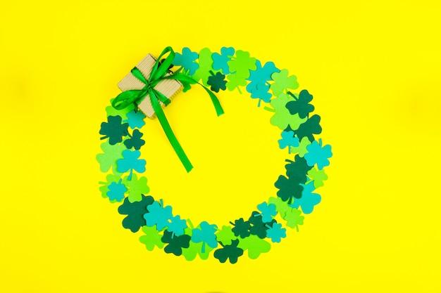 Día de san patricio. forma de círculo de tréboles de tres pétalos verdes y caja de regalo acostado fondo