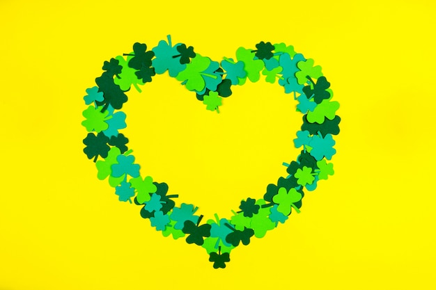 Día de san patricio. en forma de corazón de tréboles de tres pétalos verdes sobre fondo amarillo
