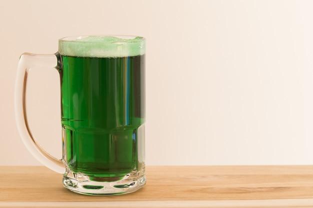 Día de san patricio. jarra de cerveza verde sobre tabla de madera