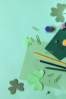 Día de san patricio, materiales de arte en la mesa, hojas de trébol decorativo,