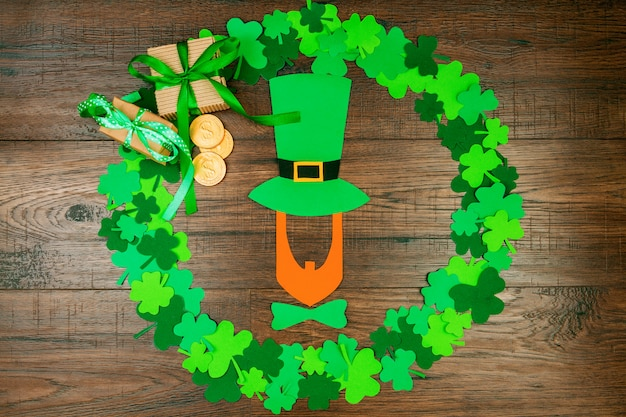 Día de san patricio. silueta de duende con sombrero acostado en la mesa de madera en forma de círculo de tréboles de tres pétalos verdes, caja de regalo y monedas de oro