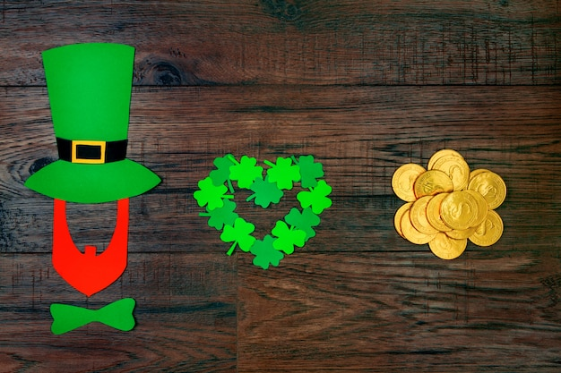 Día de san patricio. silueta de duende con sombrero verde y pajarita verde con trébol verde de tres pétalos en forma de corazón y monedas de oro en la mesa de madera