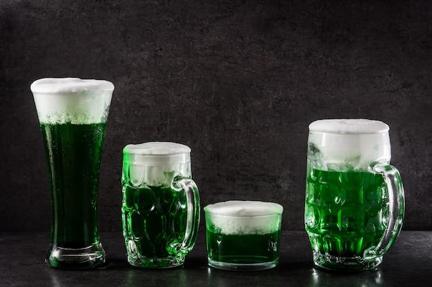 Día de san patricio tradicionales cervezas verdes sobre fondo negro.
