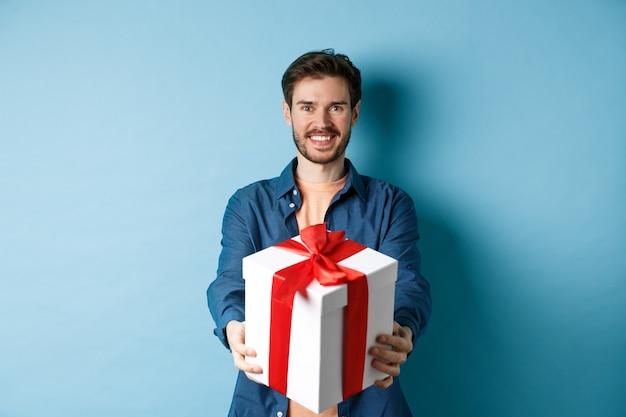 Día de san valentín. apuesto hombre sonriente extendiendo las manos con caja de regalo, deseando felices fiestas. chico haciendo presente sorpresa y mirando alegre, de pie sobre fondo azul.