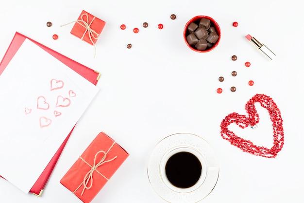 Día de san valentín con bebida de café, caja de regalo, dulces sobre fondo blanco, endecha plana