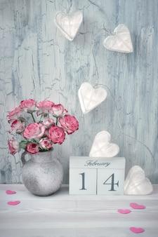Día de san valentín bodegón con calendario de madera, rosas rosadas y luces de guirnaldas en superficie rústica