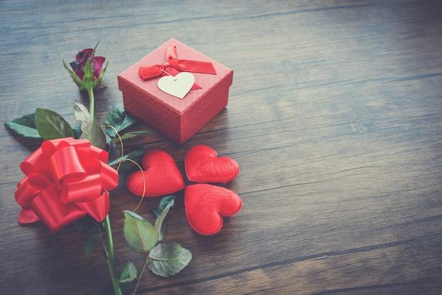 Día de san valentín caja de regalo roja sobre madera corazón rojo día de san valentín rosa roja flor y caja de arco presente en madera vieja