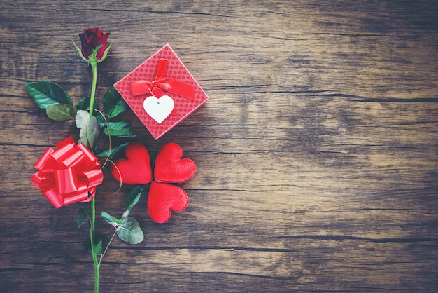 Día de san valentín caja de regalo roja sobre madera corazón rojo día de san valentín rosa roja flor y caja de arco presente