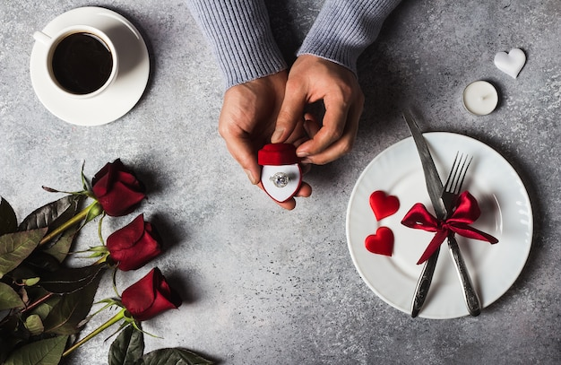 Día de san valentín cena romántica mesa ajuste hombre mano sosteniendo el anillo de compromiso
