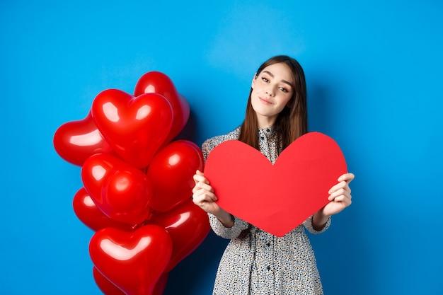 Día de san valentín. chica romántica en vestido mostrando un gran recorte de corazón rojo, soñando con amor, de pie cerca de globos de vacaciones sobre fondo azul