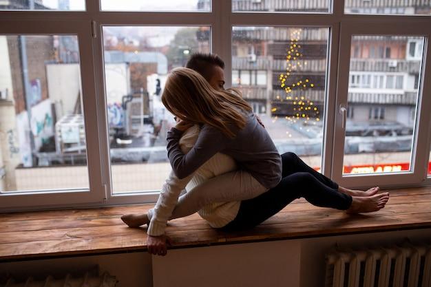 Día de san valentín. concepto de amor, felicidad, personas y diversión. hermosa pareja abrazándose mientras está sentado en el alféizar de la ventana en casa.