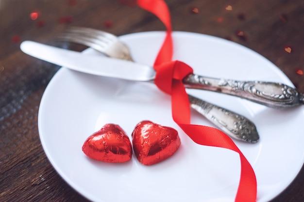 Día de san valentín configuración de la mesa festiva, maqueta con dos caramelos de chocolate con forma de corazón rojo
