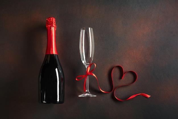 Día de san valentín con copas de champán y una cinta en forma de corazón.