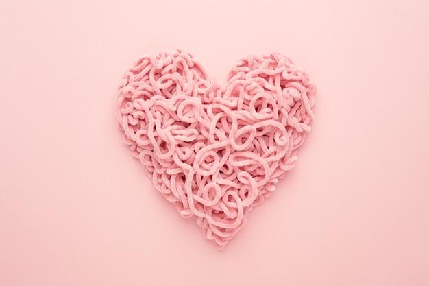Día de san valentín corazón de hilo sobre fondo rosa. copie el espacio, endecha plana. símbolo de amor compuesto.