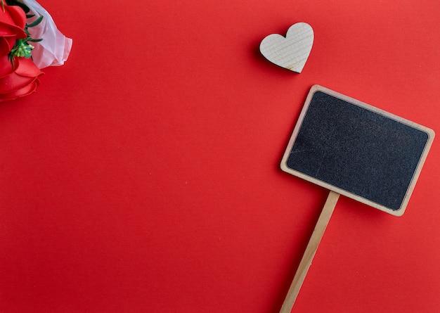 Día de san valentín corazón de madera sobre fondo rojo