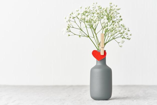 Día de san valentín. delicadas flores blancas en un jarrón. corazón de fieltro rojo - símbolo de los amantes