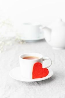 Día de san valentín. desayuno de la mañana para dos con té y flores. corazón de fieltro rojo