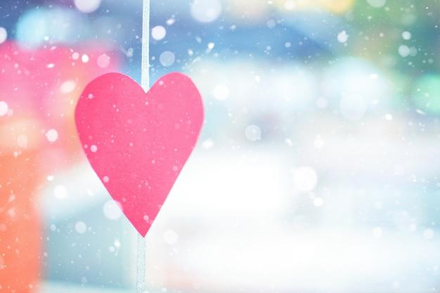 Día de san valentín en un día de invierno cubierto de nieve. decoración de papel rojo tallado en forma de corazón.