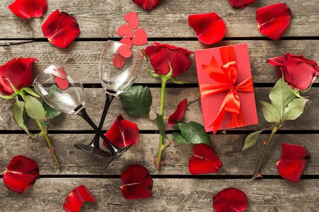 Día de san valentín día de la madre caja de regalo roja con flores pétalos de rosa corazones de papel y copas de vino en la mesa de madera vista