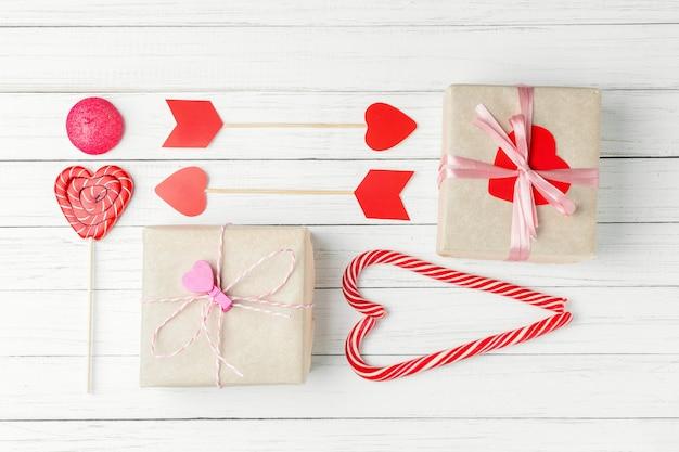 Día de san valentín con dulces, caja de regalo y papel cortado corazón en blanco