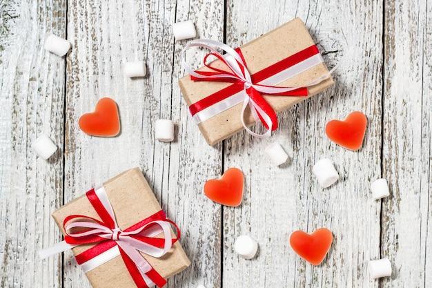 Día de san valentín dulces corazones malvaviscos y caja de regalos en papel artesanal sobre fondo blanco de madera