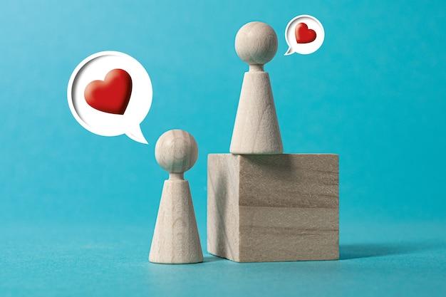 Día de san valentín figuras de madera hablan de amor fondo azul