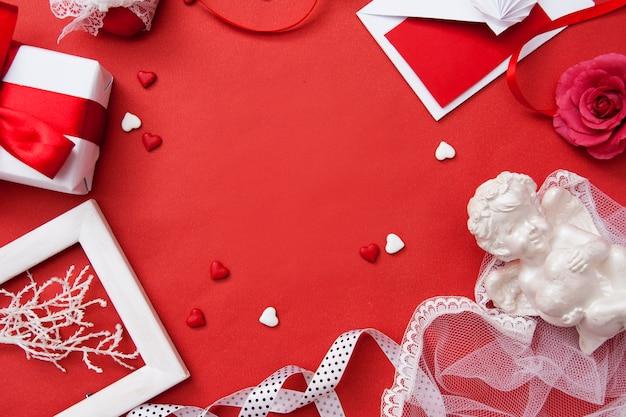 Día de san valentín flat lay. regalo, sobre, corazón y corazones sobre fondo rojo con