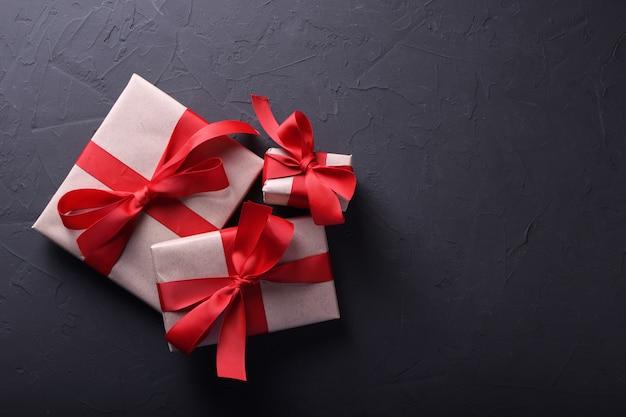 Día de san valentín fondo tarjeta de felicitación símbolos de amor, decoración roja con cajas de regalos sobre fondo de piedra. vista superior con espacio de copia y texto.