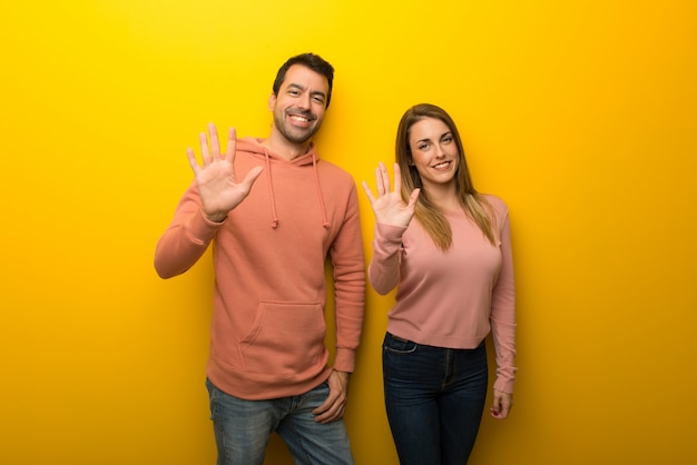 En el día de san valentín grupo de dos personas sobre fondo amarillo contando cinco con los dedos