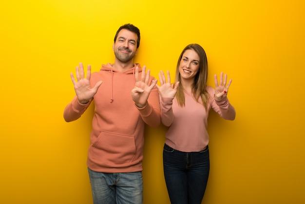 En el día de san valentín grupo de dos personas sobre fondo amarillo contando nueve con los dedos