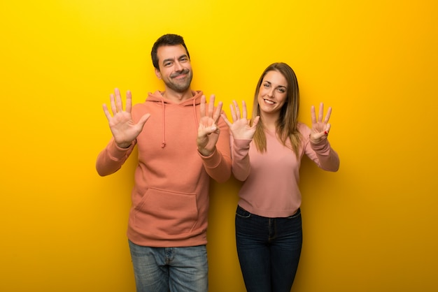 En el día de san valentín grupo de dos personas sobre fondo amarillo contando ocho con los dedos