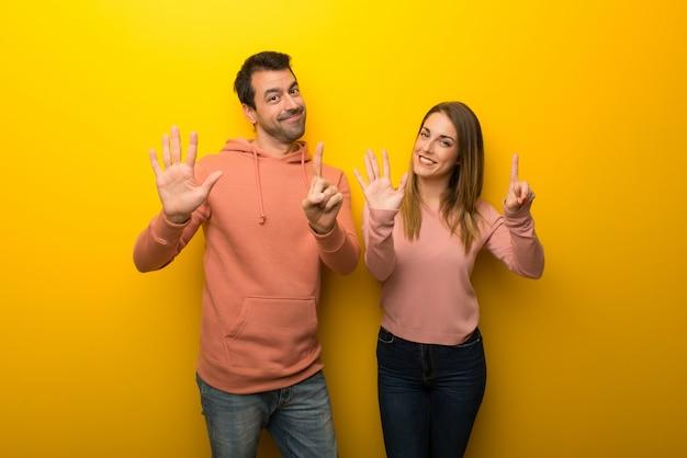 En el día de san valentín grupo de dos personas sobre fondo amarillo contando seis con los dedos