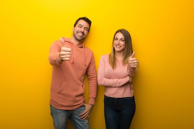 En el día de san valentín grupo de dos personas sobre fondo amarillo dando un pulgar hacia arriba gesto porque algo bueno ha sucedido