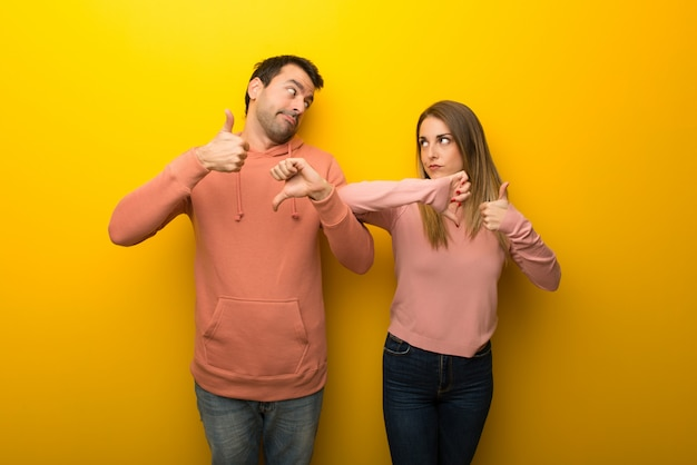 En el día de san valentín grupo de dos personas sobre fondo amarillo haciendo señales buenas-malas indecisa entre sí o no