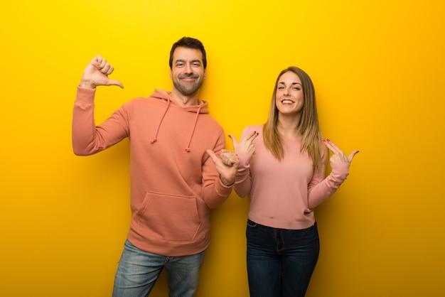 En el día de san valentín grupo de dos personas sobre fondo amarillo orgullosos y satisfechos con el concepto de amor propio