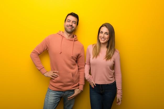 En el día de san valentín grupo de dos personas sobre fondo amarillo posando con los brazos en la cadera y sonriendo