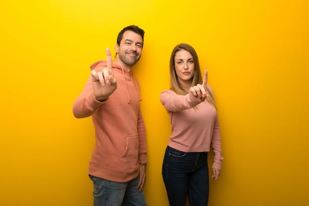 En el día de san valentín grupo de dos personas sobre fondo amarillo que muestra y levanta un dedo