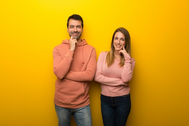 En el día de san valentín grupo de dos personas sobre fondo amarillo sonriendo con una expresión dulce