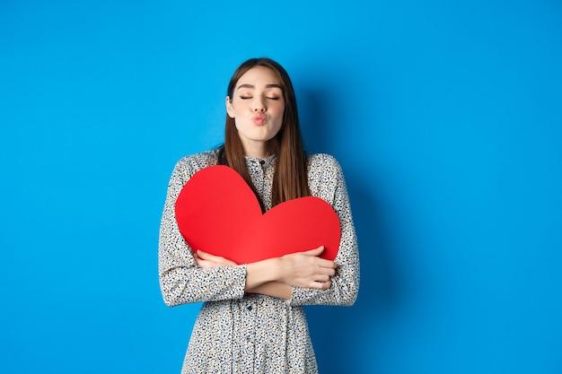 Día de san valentín. hermosa mujer romántica cierra los ojos y frunce los labios para besar, sosteniendo un gran recorte de corazón rojo, besándote, de pie sobre fondo azul.