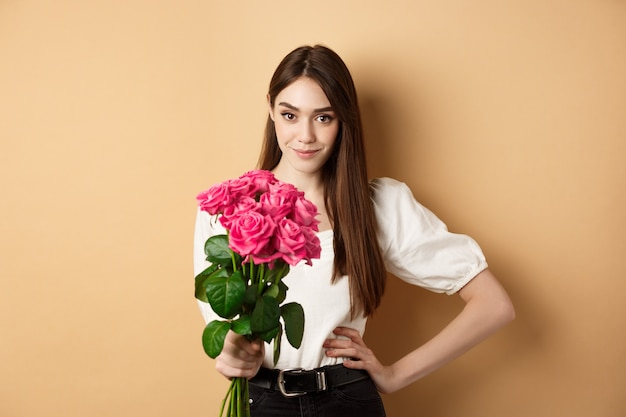 Día de san valentín hermosa novia sosteniendo rosas rosadas y mirando a cámara mujer joven recibe flo ...