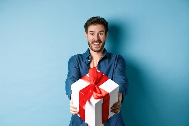 Día de san valentín. hombre guapo emocionado dando caja de regalo y deseando felices fiestas. chico romántico extendiendo las manos con el presente, de pie contra el fondo azul.