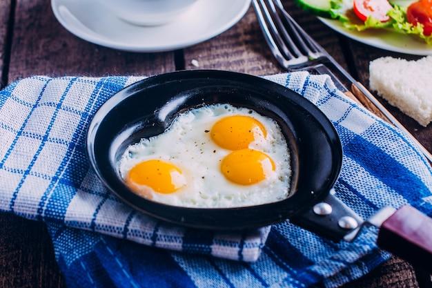 Día de san valentín. huevos revueltos en forma de corazones, café negro y plato con verduras