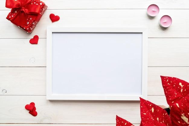 Día de san valentín. marco blanco con decoraciones de san valentín velas, regalos y confeti vista superior sobre fondo blanco de madera