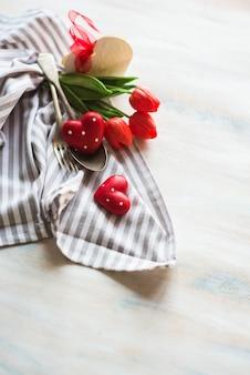 Día de san valentín con mesa, flores y corazones.