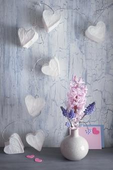 Día de san valentín o celebración de primavera, florero con flores de jacinto y luces de guirnaldas con corazones de papel