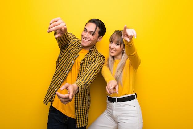 En el día de san valentín pareja joven sobre fondo amarillo vibrante apunta con el dedo mientras sonríe