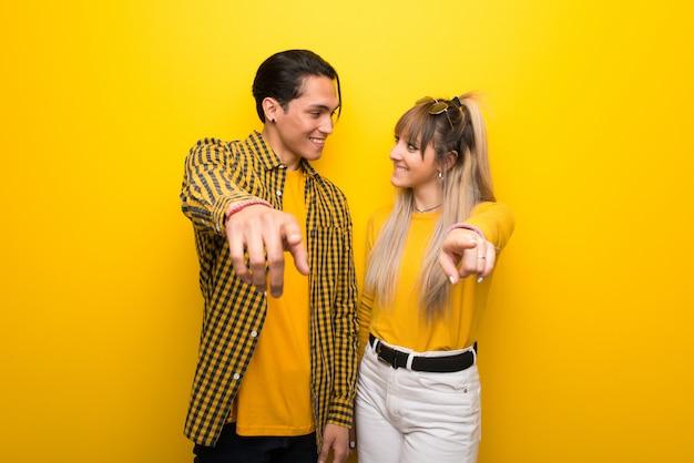 En el día de san valentín, una pareja joven sobre un fondo amarillo vibrante te señala con un dedo con una expresión de confianza.