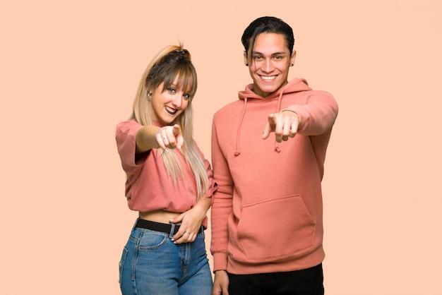 En el día de san valentín, una pareja joven te señala con el dedo con una expresión de confianza sobre un fondo rosa.