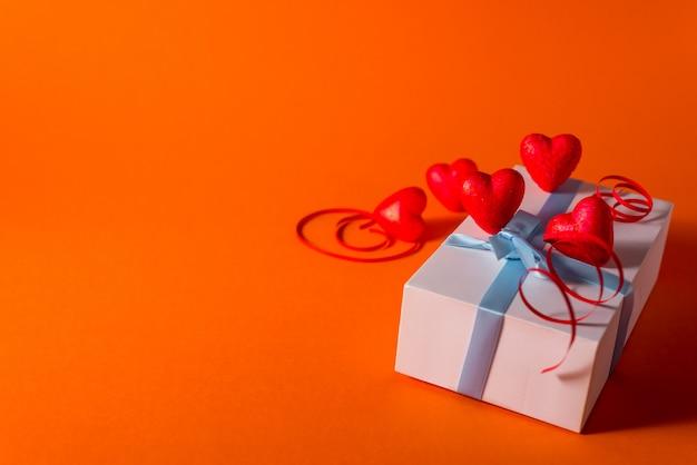 Día de san valentín romántico abstracto satén corazones y cinta de fondo. fondo rojo anaranjado con corazones