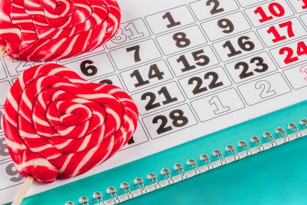 Día de san valentín rosa claro, concepto de tarjeta de felicitación, dos piruletas de corazón rojo o dulces dulces en palos y calendario, copyspace